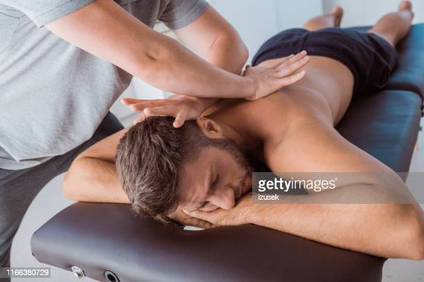 man receiving relaxing back massage - sports medicine stock pictures, royalty-free photos & images