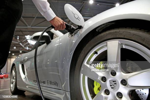 A man recharges the prototype of a Porsche Boxster E car model during a conference on electro mobility in Leipzig Germany 14 April 2016 The German...