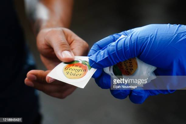 "Man recieves an ""I'm a Georgia Voter"" sticker after casting a ballot in Georgia's Primary Election on June 9, 2020 in Atlanta, Georgia. Voters in..."
