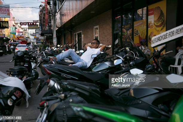 A man reclines at a spot for motorbike rentals on March 23 2020 in Pattaya Thailand On March 18th Pattaya announced the closure of schools bars and...