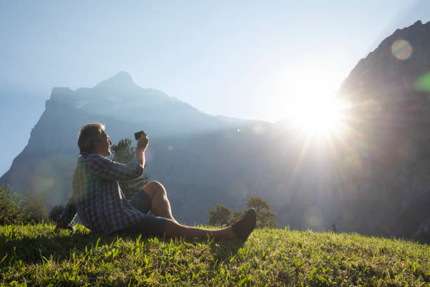 Man reclines in a lush mountain meadow and takes photo with his cell phone