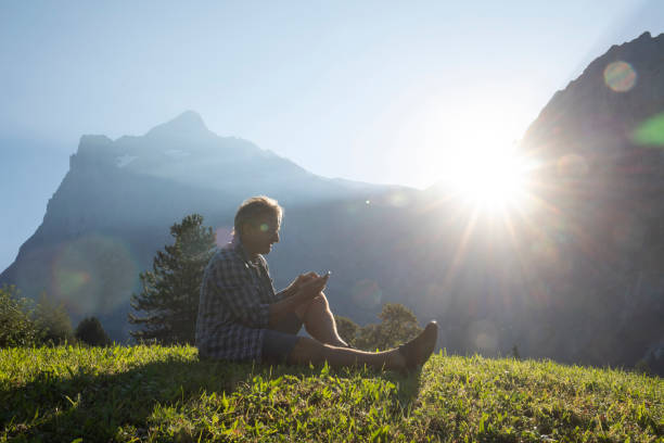 Man reclines in a lush mountain meadow and uses his cell phone