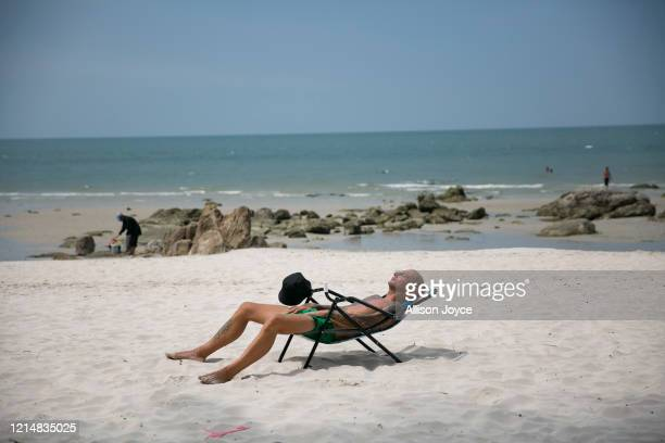 Man reclines on the beach on May 24, 2020 in Hua Hin, Thailand. As the province of Prachuap Khiri Khan signed orders to re-open hotels last week,...