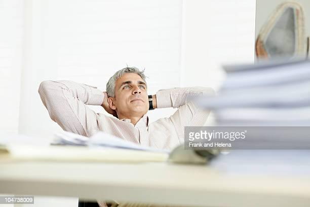 man reclining behind desk - zurücklehnen stock-fotos und bilder
