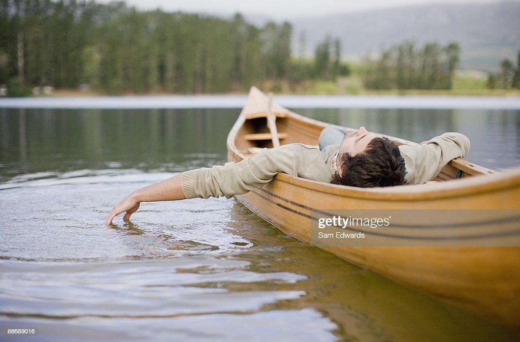 Man reclining in canoe on lake : Stock Photo