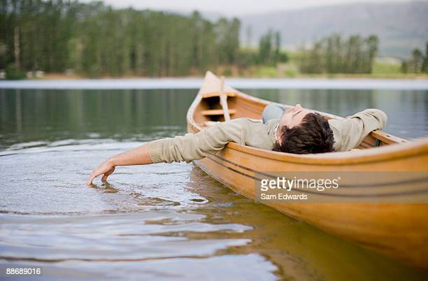 man reclining in canoe on lake - rowing boat stock pictures, royalty-free photos & images
