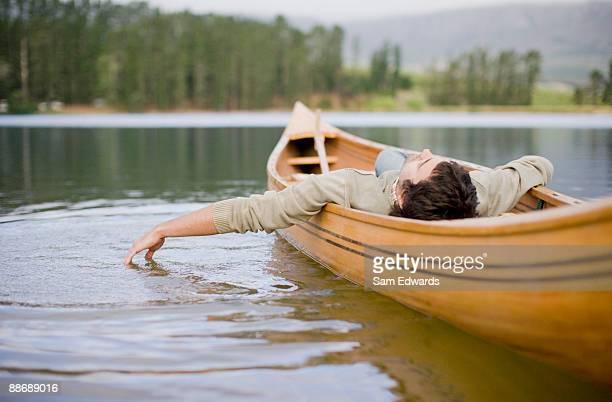 Uomo sdraiato in canoa sul lago