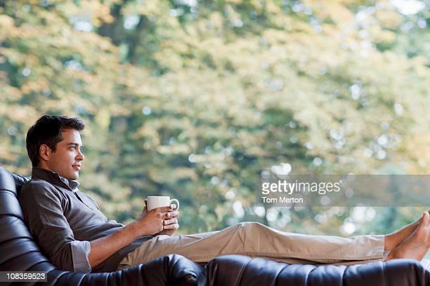 Hombre bebiendo café en una silla reclinable