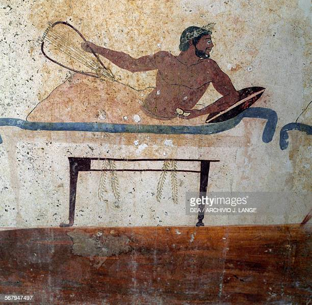 Man reclining on a triclinium bed fresco on the south wall of the Tomb of the Diver Paestum Campania Italy Ancient Greek civilisation 5th century BC...