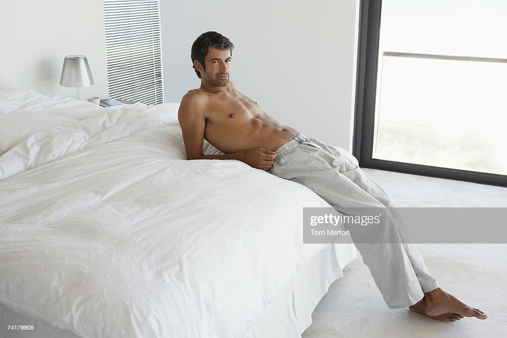 Man reclining on bed : Stock Photo