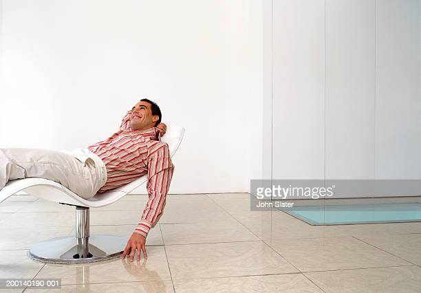 man reclining on chair, fingers touching floor - reclining chair stock photos and pictures