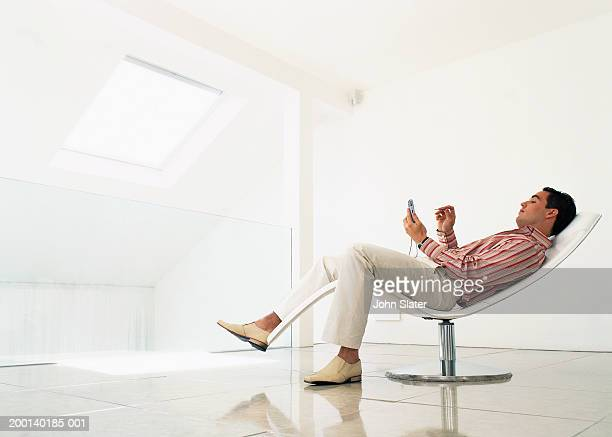 Man reclining on chair using electronic organiser, side view