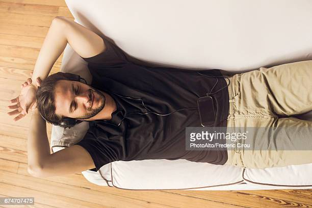 Man reclining on couch listening to music playing on smartphone