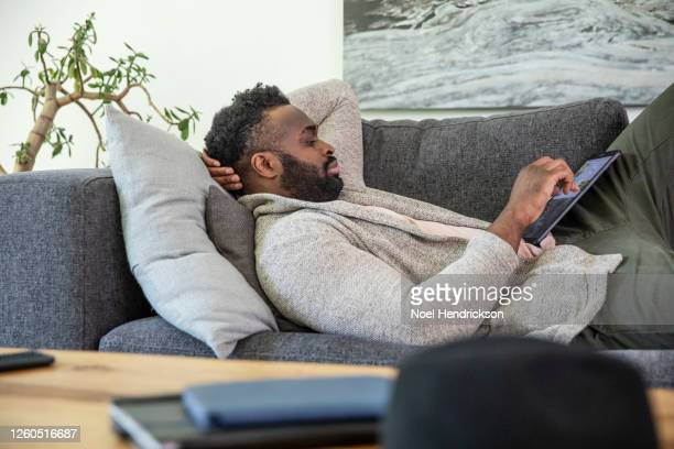 man reclining on couch using a tablet computer - mid adult men stock pictures, royalty-free photos & images