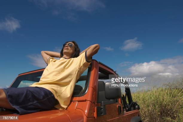 Man reclining on hood of jeep under blue sky