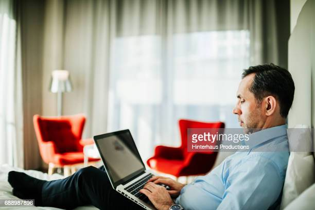 man reclining on hotel bed using his laptop - human body part stock pictures, royalty-free photos & images