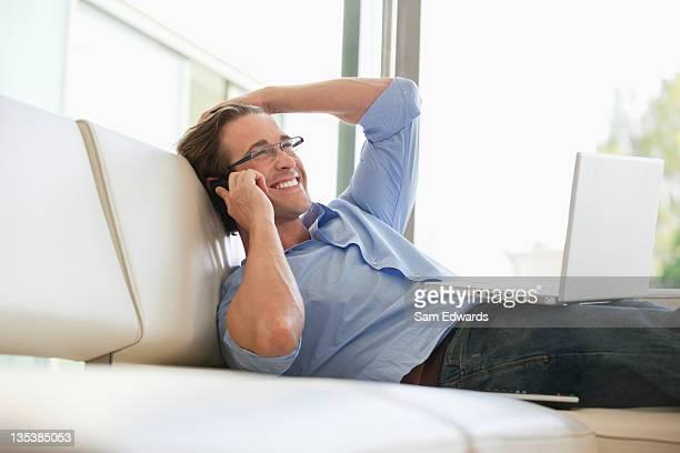 Mann ruhen auf sofa Gespräch am Handy