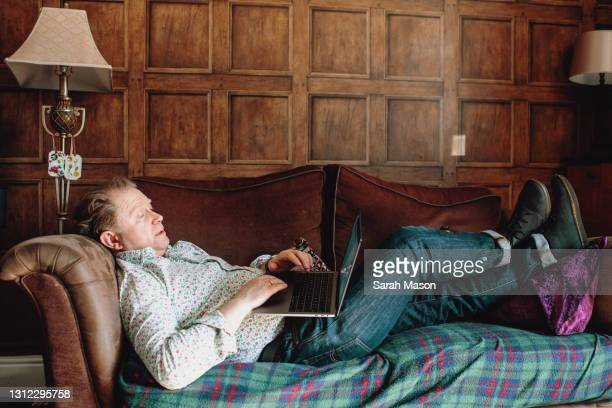man reclining on sofa whilst on laptop - lying down stock pictures, royalty-free photos & images