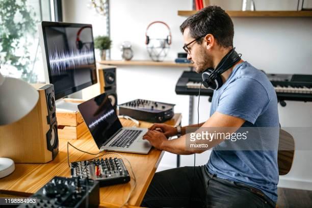 mann nimmt neue musik auf soundmixer im heimischen studio auf - produzent stock-fotos und bilder