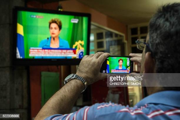 TOPSHOT A man records with his cell phone the speech of Brazilian President Dilma Roussef on tv in Rio de Janeiro Brazil on April 18 Brazil President...