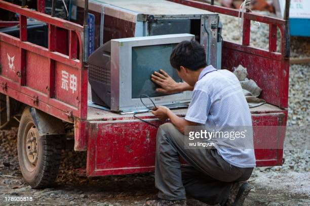 CONTENT] man recycling old appliances was cleaning the screen of an old TV at Zhaoxing Dong villageGuizhou