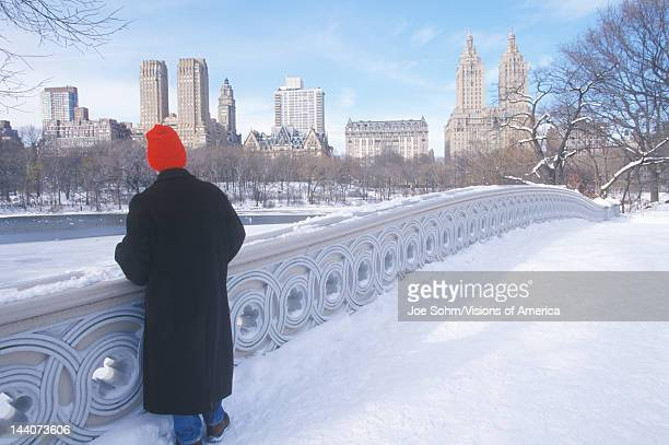 Man Red stocking cap looks at pond in fresh snow in Central Park Manhattan New York City NY