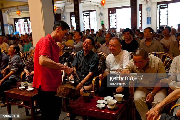 Man refilling the tea cups for audiences enjoying Sichuan Opera