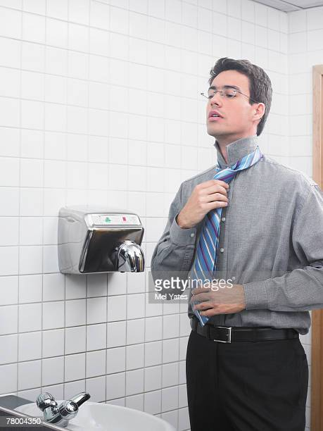 Man reflected in office washroom mirror doing up his tie