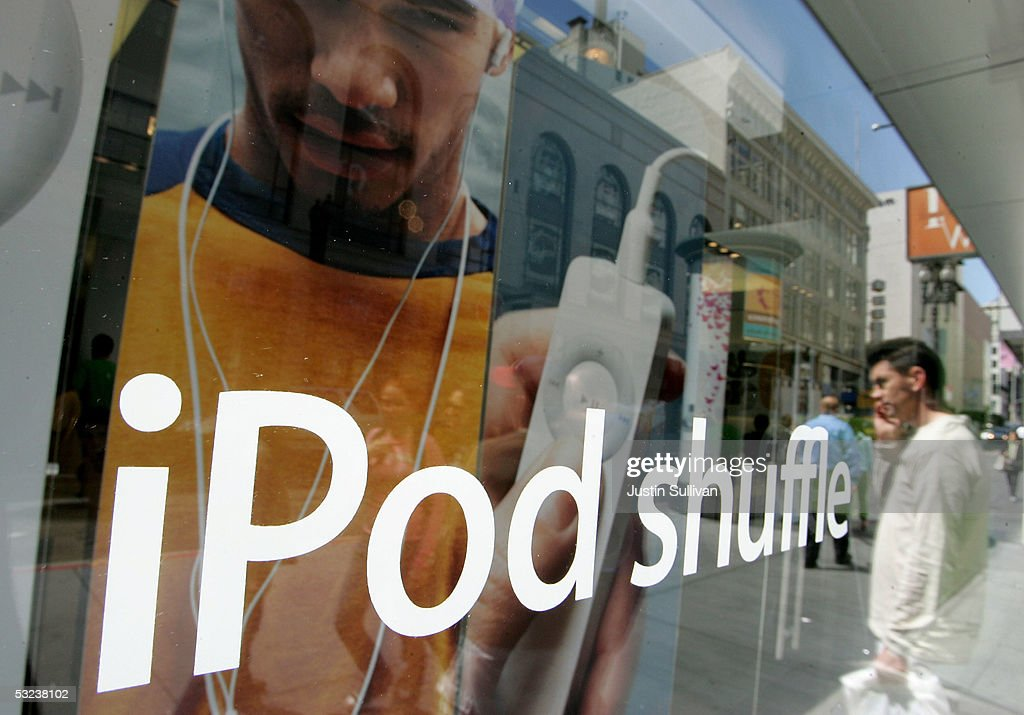 A man, reflected in plate glass, looks at a window display for the iPod Shuffle at the Apple Store July 14, 2005 in San Francisco, California. Shares of Apple Computer surged Thursday after the company reported its best quarterly profit ever. Apple?s net income rose to $320 million, or 37 cents per share, up from the $61 million and 8 cents per share the company reported in the same quarter last year.