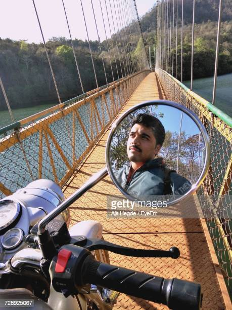 Man Reflecting In Motorcycle Side-View Mirror On Suspension Bridge Over River
