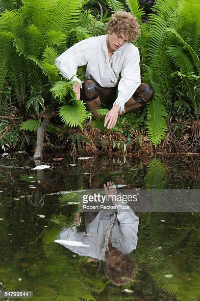 man reflecting in pond - narcissus mythological character stock photos and pictures