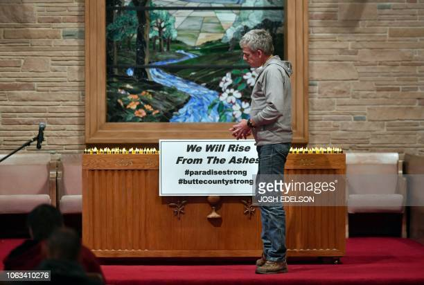 A man reflects after leaving a candle on a table onstage during a vigil for victims of the Camp fire at First Christian Church in Chico California on...