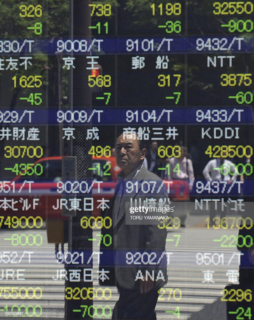 A man reflects on an electric quotation board flashing share prices of the Tokyo Stock Exchange (TSE) in front of a securities company in Tokyo on May 21, 2010. Japanese shares plunged 2.51 percent by noon following Wall Street's biggest drop in more than a year and as the continued strength of the yen prompted investors to sell shares. AFP PHOTO/Toru YAMANAKA