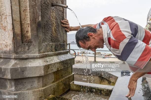 Man refreshes himself in a fountain during a hot summer day in Messina, on August 11, 2021.