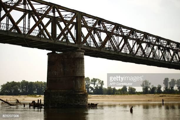 A man refreshes himself in the Po River under the Ponte della Becca bridge in Linarolo near Pavia northern Italy on August 1 as the country is...