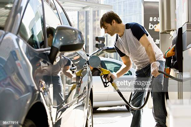 Man refueling vehicle at gas station
