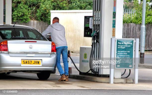 Man refuels at a Morrisons petrol station selling unleaded petrol at 99.7p per litre, the first time since 2016 petrol has been sold below £1 per...