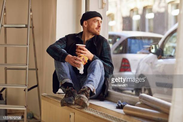 man refurbishing shop location, sitting on windowsill, drinking coffee - resting stock pictures, royalty-free photos & images