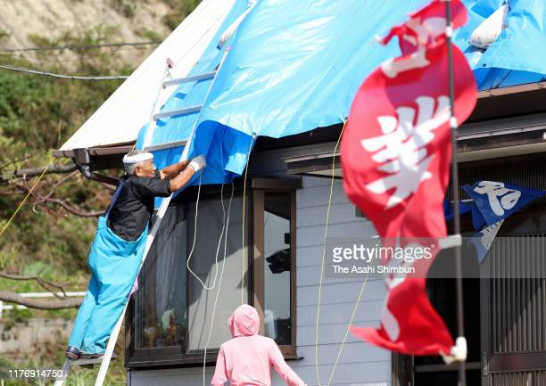 A man reinforces tarps on the roof as strong wind caused by Typhoon Tapah blows on September 23 2019 in Nobeoka Miyazaki Japan