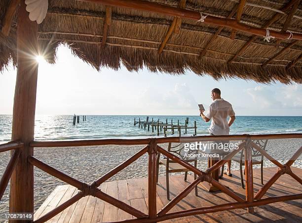 man relaxes against beach palapa, uses tablet - parasol de plage photos et images de collection