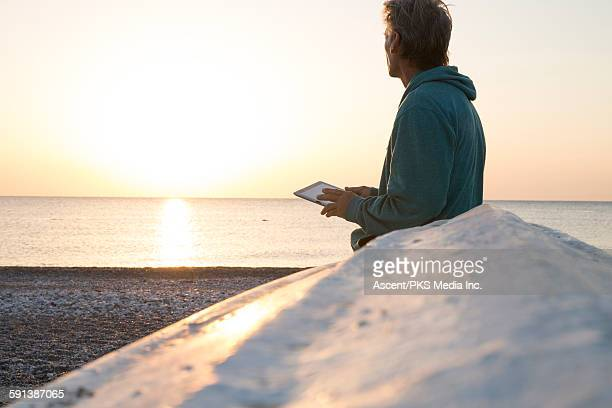 Man relaxes against flipped boat, w digital tablet
