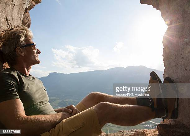 Man relaxes in ancient window frame, above valley