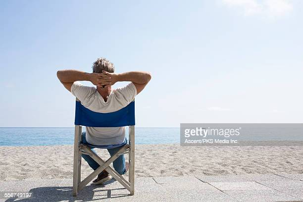 man relaxes in beach chairs, looks out to sea - hands behind head stock pictures, royalty-free photos & images