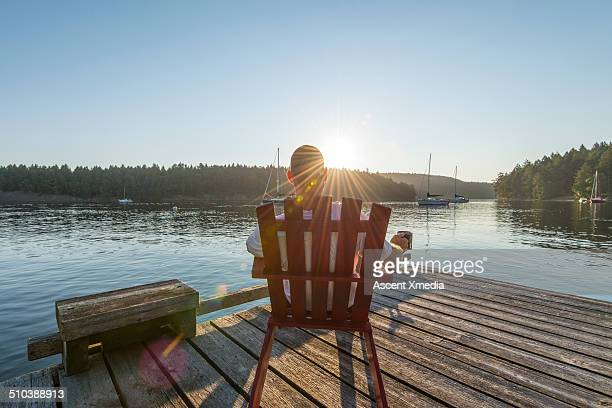 Man relaxes in chair on wooden pier, seaside