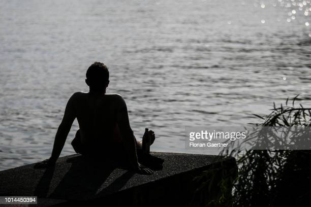 A man relaxes in front of the canal Landwehrkanal on August 09 2018 in Berlin Germany