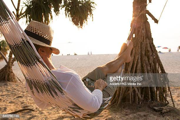 Man relaxes in hammock, sleeps under hat