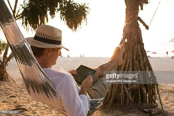 Man relaxes in hammock, uses digital tablet