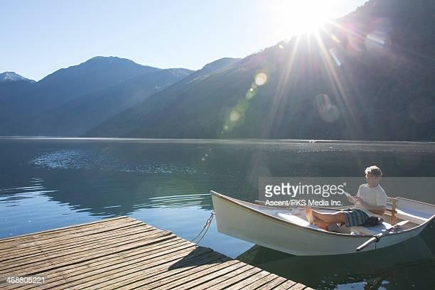 man relaxes in rowboat, uses digital tablet - bateau à rames photos et images de collection