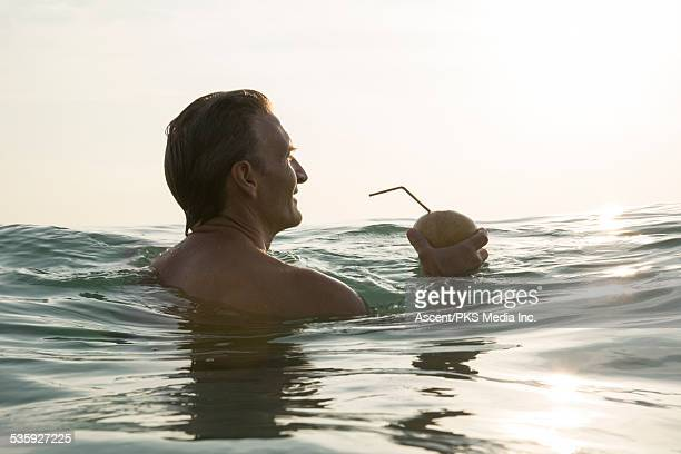 Man relaxes in sea shallows, sipping coconut