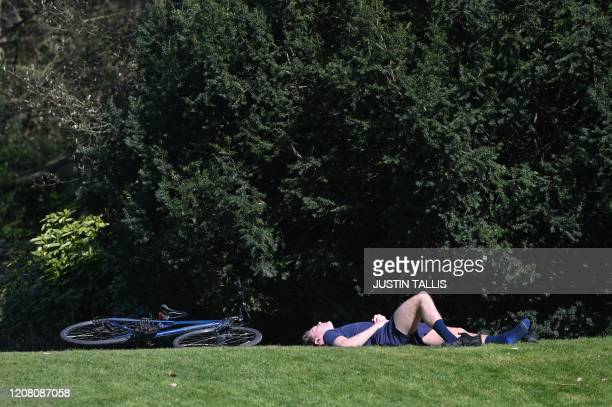 A man relaxes in the Spring sunshine in Battersea Park in London on March 24 2020 after Britain's government ordered a lockdown to slow the spread of...